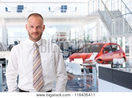 Portrait of car salesman in showroom, looking at camera, smiling.