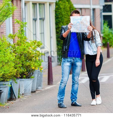 Young family with a map outdoors in Amsterdam