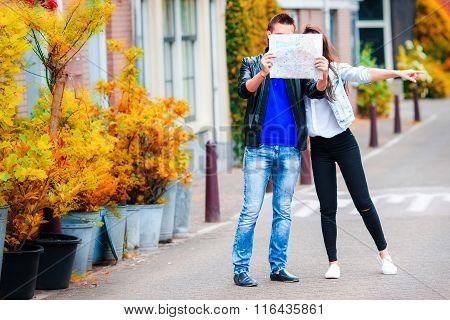 Young couple with a map outdoors