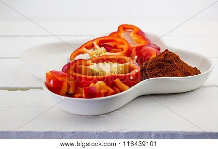 White Plate With Red Capsicum And Paprika Spice Isolated On Rustic White Table
