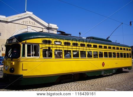 Yellow And Green Tram At Pier 15 In San Francisco, California Usa