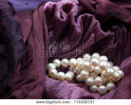 Pink Cultured Pearls On Burgundy Velvet Crumpled Dress Background
