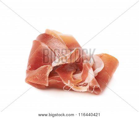 Folded prosciutto ham slice isolated