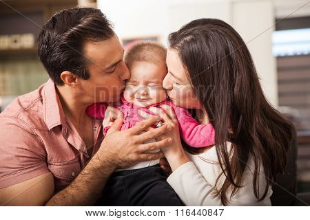 Parents Kissing Baby At The Same Time