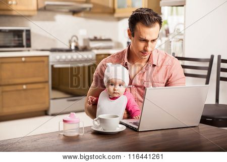 Young Single Dad Working At Home With His Baby
