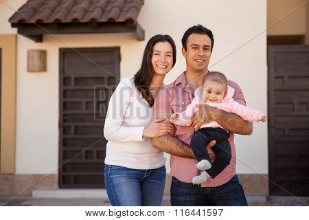 Hispanic Couple And Baby In Their New Home