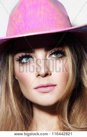 Portrait of young beautiful blonde girl with stylish make-up in party pink cowboy hat
