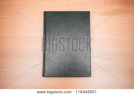 Book With Empty Black Cover Laying On Wooden Table