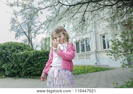 Outdoor spring portrait of preschooler girl looking at little pocket mirror in spring yard