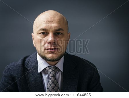 Portrait of an adult man in a business suit on a black background. Unhappy and thoughtful businessman.