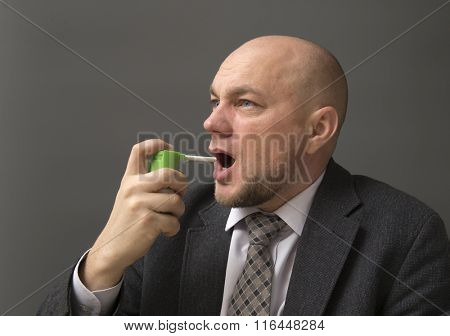 Portrait of an adult man in a business suit on a black background. Using Inhaler