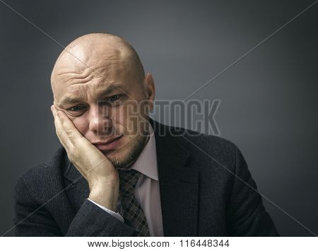 Portrait of an adult man in a business suit on a black background. Man with a toothache tooth pain