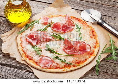 Pizza with prosciutto and mozzarella on wooden table. Closeup
