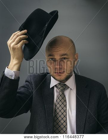 Portrait of an adult man in a business suit on a black background.