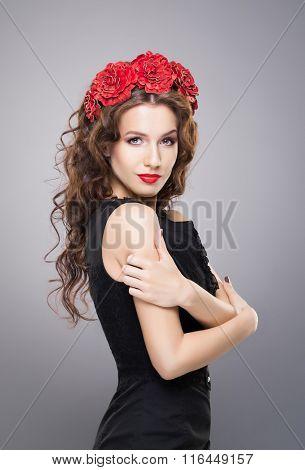 Beautiful brunette with bright red lipstick wearing flower alike headband over grey background.
