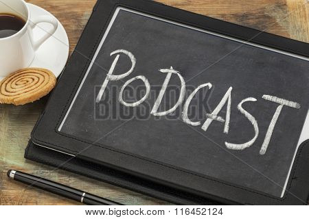 podcast word in white chalk against blackboard on a digital tablet wit a cup of coffee