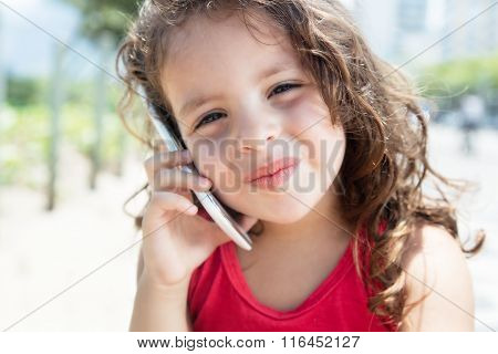 Cute Child In A Red Shirt Listening At Mobile Phone Outside
