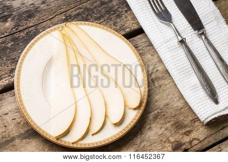 Sliced Pear On Saucer With Silverware On The Table