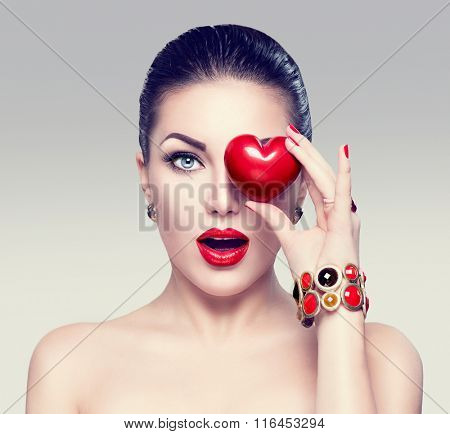 Fashion woman with red heart. Valentine's day art portrait. Beautiful make up and manicure. Surprised model girl face, open mouth, emotion