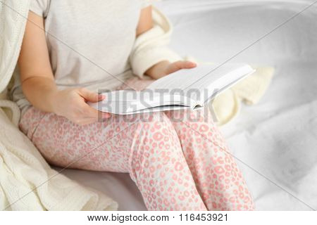 Woman in pajamas reading a book on her bed