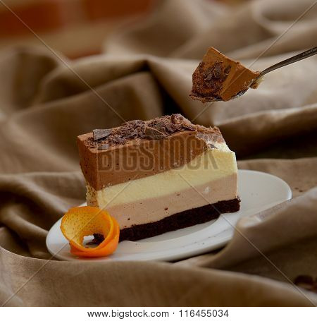 delicious piece of layered cake on white plate with a little spoon