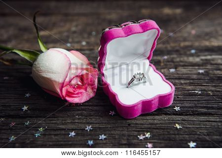 A Diamond Engagement Ring In A Jewellery Box, Shot Next To A Red Rose