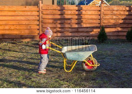 Little Girl Pushing Garden Wheelbarrow
