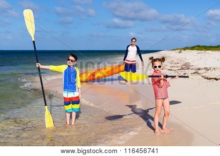 Family father and kids pulling colorful kayaks after paddling at tropical ocean water during summer vacation
