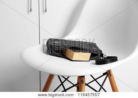 Fashion female handbag with book on white chair