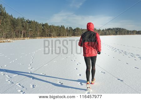 Man running outdoors on snow covering in winter nature