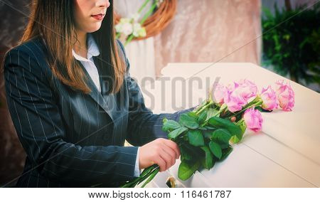 Woman putting rose on coffin at funeral