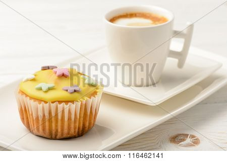 Muffins covered with icing sugar on white plate and cup of coffee.