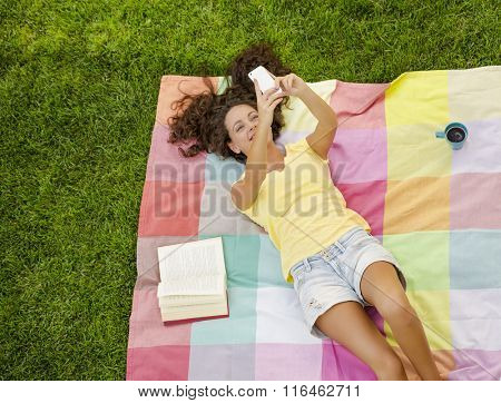 Smiling young woman lying on a blanket and making a selfie
