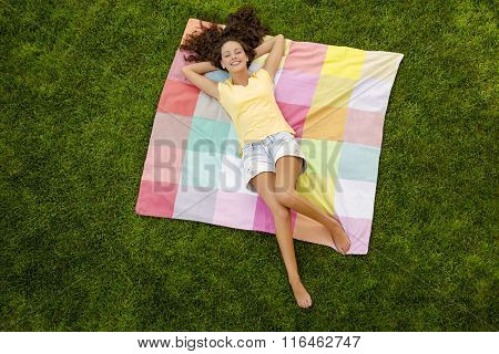 Smiling young woman lying on her back on a blanket and relaxing
