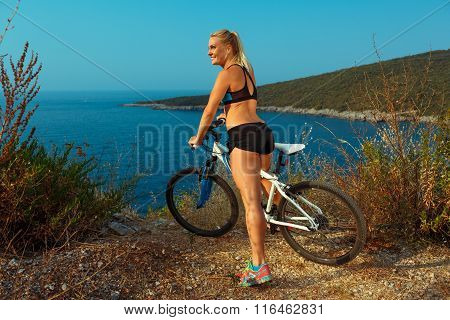 Woman Cyclist On A Mountain Bike Looking At The Landscape Of Mountains And Sea