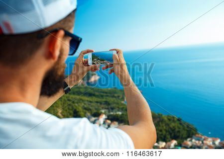 Man Makes Photos By A Smartphone On The Background Of Sea Coast, Adriatic Sea