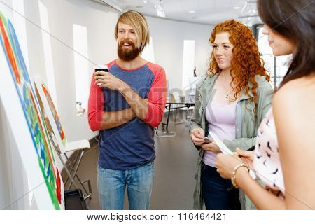 Young people standing in a gallery and contemplating artwork