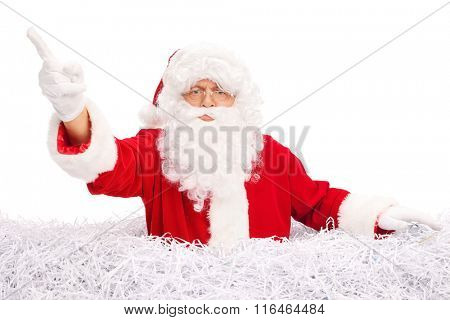 Angry Santa Claus pointing with his finger and standing in a pile of shredded paper isolated on white background
