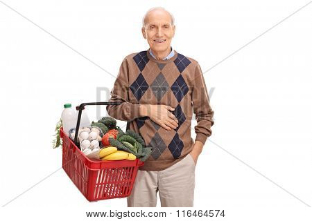 Cheerful senior gentleman holding a shopping basket full of groceries isolated on white background