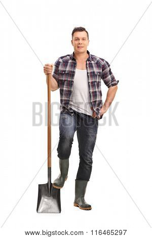 Full length portrait of a male manual worker holding a shovel isolated on white background