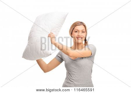 Studio shot of a young cheerful woman having a pillow fight and swinging with a pillow isolated on white background