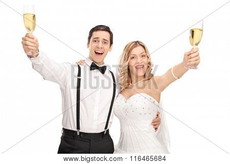 Young newlywed couple making a toast towards the camera with white wine isolated on white background