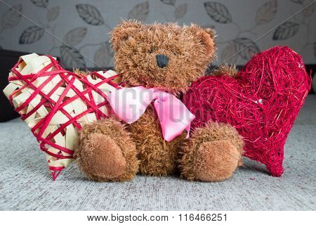 Valentines Teddy Bear with red hearts sitting alone