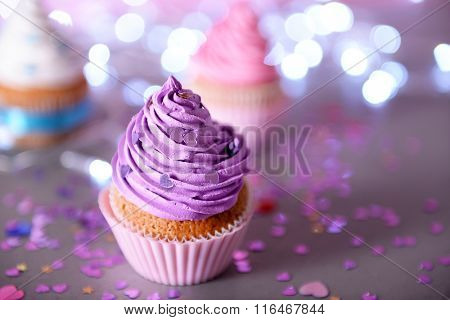 Cupcake with purple cream icing on a glitter background, close up