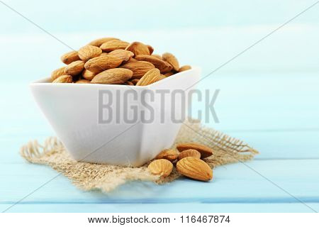 Almond kernels in the bowl on blue wooden background