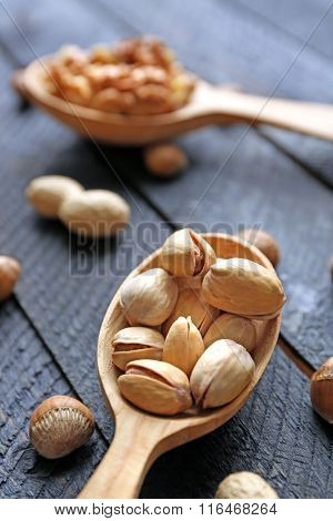 Spoons with walnuts, pistachios and peanuts, on grey wooden background