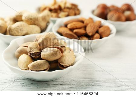 Pistachios, almonds, peanuts, walnut kernels and hazelnuts in the bowls on white wooden table, close-up