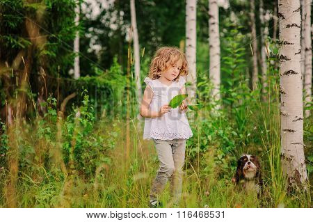 cute child girl playing with leaves in summer forest with her dog. Nature exploration with kids