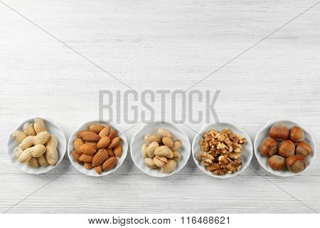 Pistachios, almonds, peanuts, walnut kernels and hazelnuts in the bowls on white wooden table