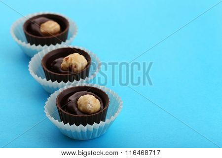 Three chocolate candies with nuts in paper cups, on blue background